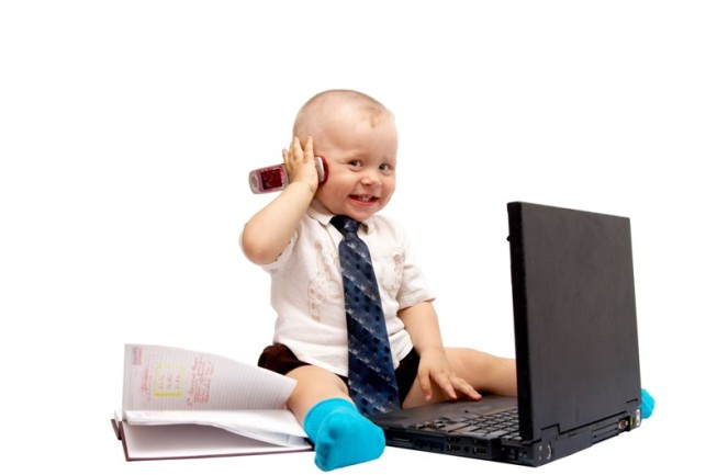The small boy sits with the computer on a white background TFGP.